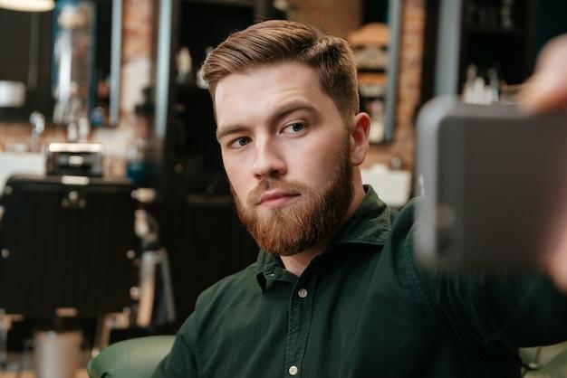 Młody człowiek siedzi w fotelu u fryzjera i weź selfie.