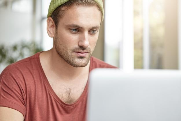 Młody człowiek siedzi w kawiarni z laptopem