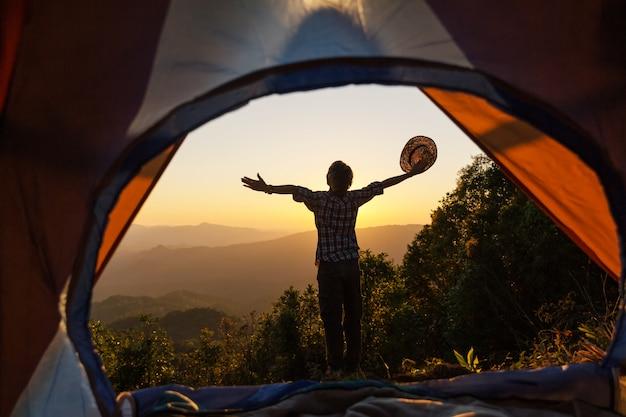 Młody człowiek siedzi w namiocie z robieniem zdjęcia z telefonu komórkowego