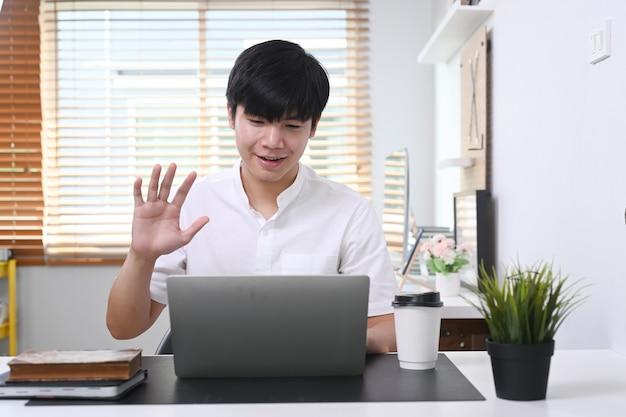 Młody człowiek siedzi w nowoczesnym biurze i wideokonferencji z kolegami na komputerze przenośnym.
