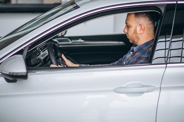 Młody człowiek siedzi w samochodzie w salonie samochodowym