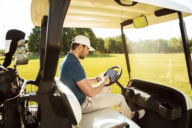 Młody człowiek siedzi w wózek golfowy z tabletem