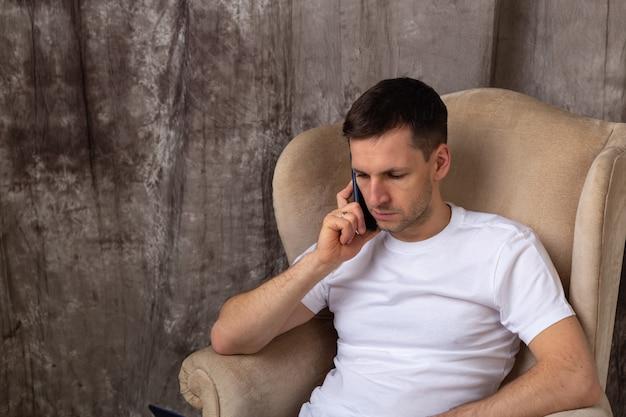 Młody człowiek siedzi wygodnie i rozmawia przez telefon