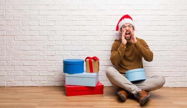 Młody człowiek siedzi z prezenty świętuje boże narodzenie krzycząc coś szczęśliwego z przodu