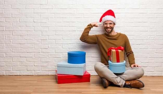 Młody człowiek siedzi z prezenty świętuje boże narodzenie, który nie poddaje się