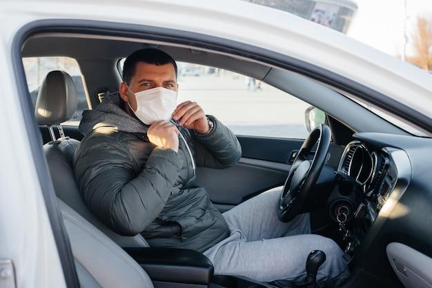 Młody człowiek siedzi za kierownicą w masce dla bezpieczeństwa osobistego podczas jazdy podczas pandemii i koronawirusa. epidemia.