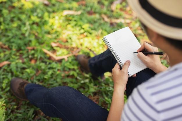 Młody człowiek siedzi za pomocą pióra, pisząc notatnik wykład notatnik do książki w parku.