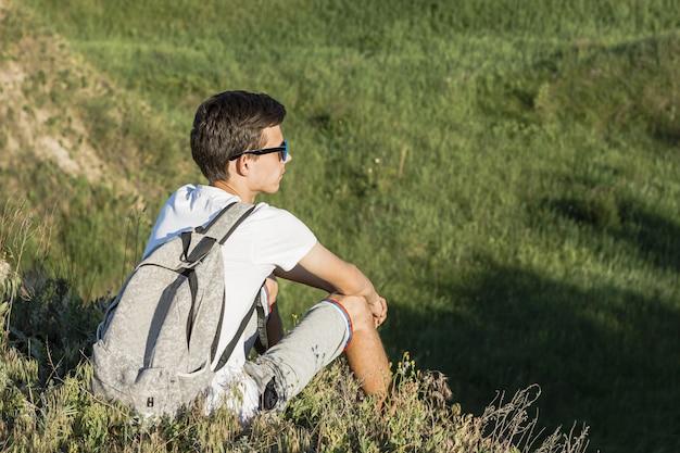 Młody człowiek siedzi zielonego widok i cieszy się