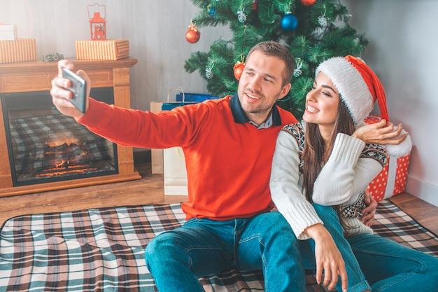 Młody człowiek siedzieć na kocu z kobietą i bierze selfie. obejmuje ją. ona pozuje i uśmiecha się.