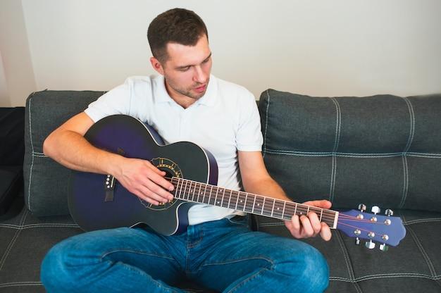 Młody człowiek siedzieć w pokoju, grając na gitarze akustycznej. uczenie się sam. trzymaj palce na strunach i graj. muzyk na zdjęciu.