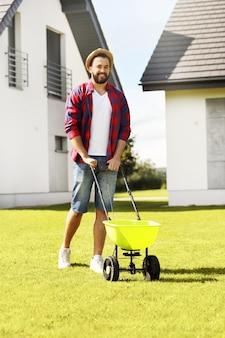 Młody człowiek sieje trawę na podwórku