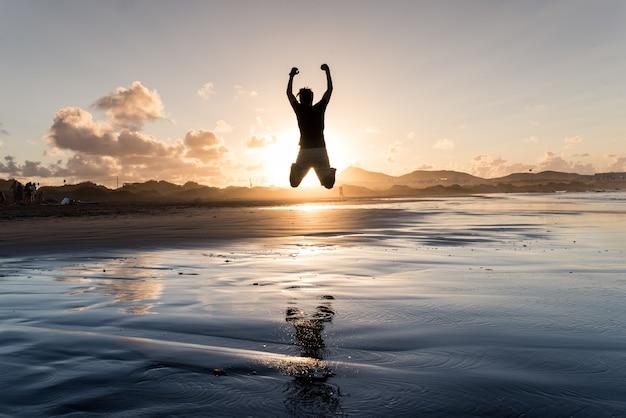 Młody człowiek skacząc nad morzem w czasie przypływu o zachodzie słońca.