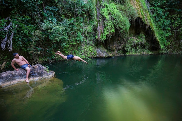 Młody człowiek skacze klif do czystej wody w dzikim wodospadzie ukrytym w zielonej letniej naturze