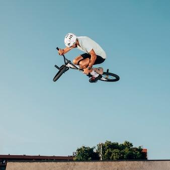 Młody człowiek skacze z rowerem bmx w skateparku