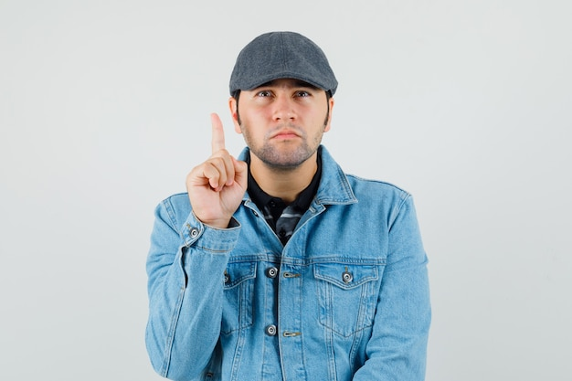 Młody człowiek skierowaną w górę w czapkę, t-shirt, kurtkę i patrząc ciekawy, widok z przodu.