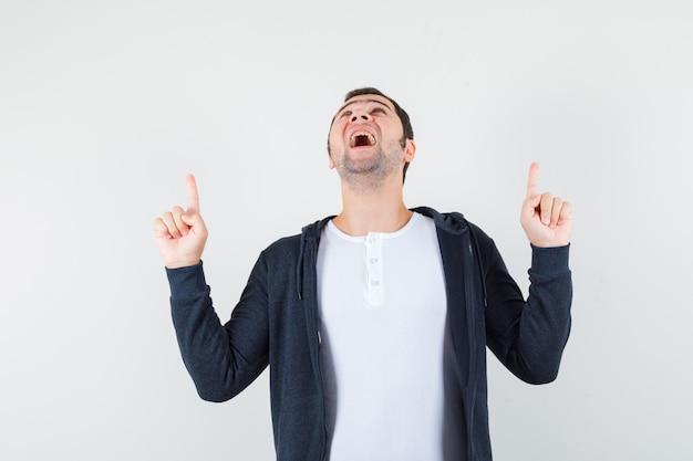 Młody człowiek skierowany w górę z palcami wskazującymi w białej koszulce i czarnej bluzie z kapturem na suwak i wygląda optymistycznie. przedni widok.