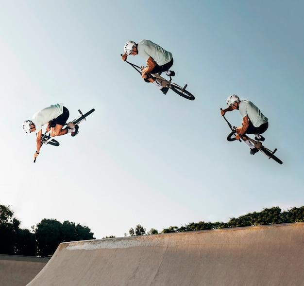 Młody człowiek skoki z rowerem bmx w skate parku