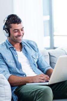Młody człowiek słucha muzyka podczas gdy używać laptop