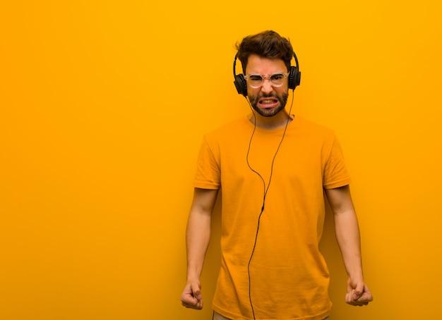 Młody człowiek słucha muzyki krzyczącej bardzo zły i agresywny
