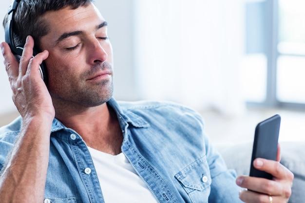 Młody człowiek słucha muzyki podczas gdy używać telefon komórkowego