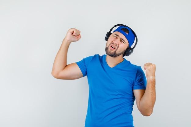 Młody człowiek słucha muzyki, pokazując gest zwycięzcy w niebieskiej koszulce i czapce