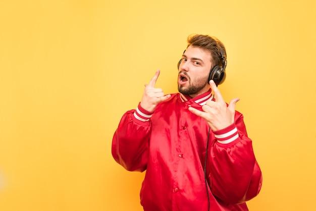 Młody człowiek słucha muzyki rockowej i pokazuje gest heavy metalu.
