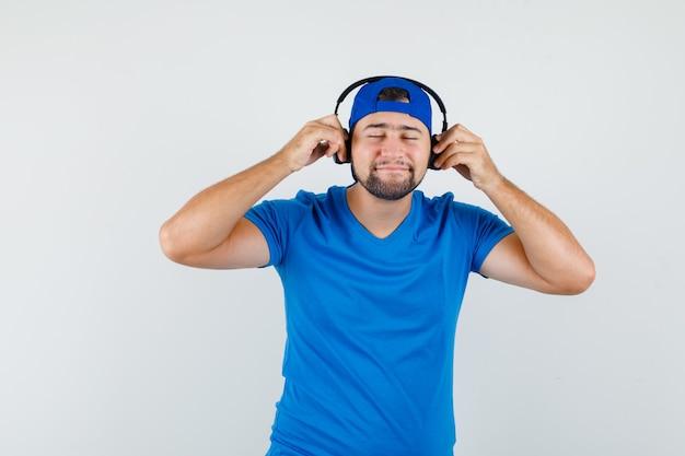 Młody człowiek słucha muzyki w słuchawkach w niebieskiej koszulce i czapce i wygląda na zrelaksowanego
