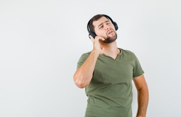 Młody człowiek słucha muzyki w słuchawkach w zielonej koszulce i szuka podpity