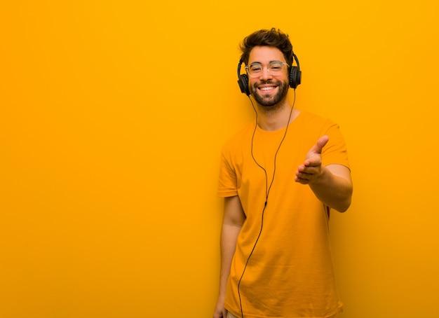 Młody człowiek słucha muzyki, wyciągając rękę, aby kogoś powitać