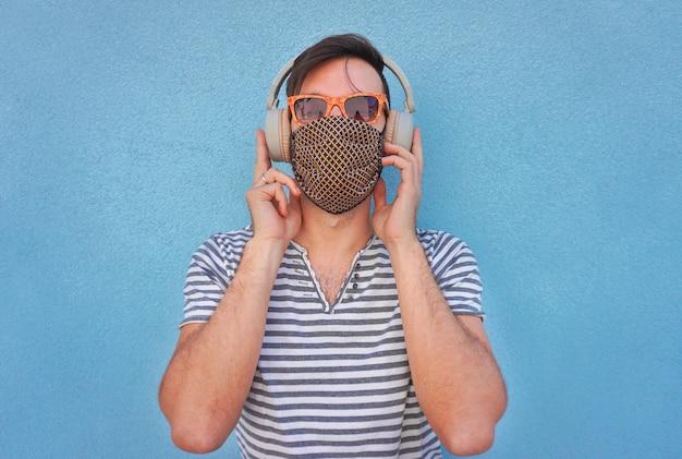 Młody człowiek słucha muzyki z dużymi słuchawkami i maską na twarz w czasie koronawirusa - chłopiec w lecie jasnym tle czuje się wesoły w odległości społecznej z okularami przeciwsłonecznymi