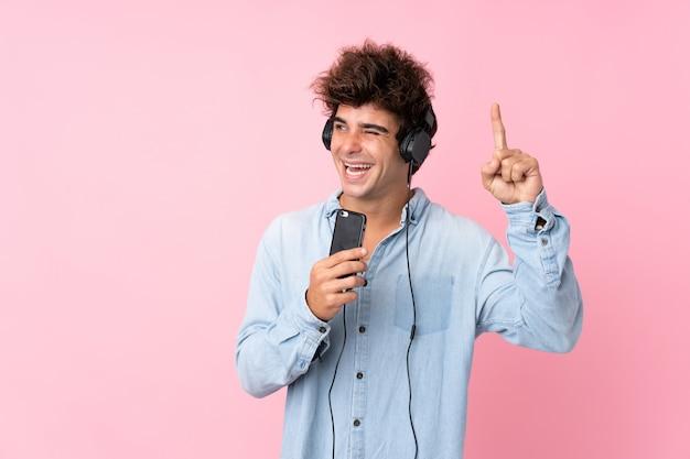 Młody człowiek słucha muzyki z smartphone i słuchawkami