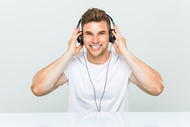 Młody człowiek słuchania muzyki w słuchawkach szczęśliwy, uśmiechnięty i wesoły.