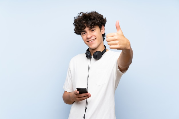 Młody człowiek słuchania muzyki z telefonu komórkowego na izolowanych niebieską ścianą z kciuki do góry, ponieważ stało się coś dobrego