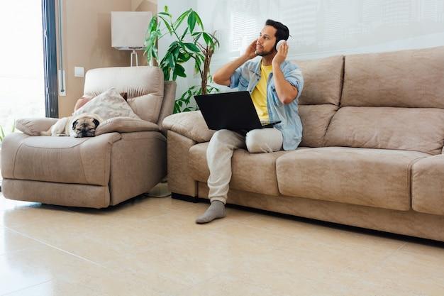 Młody człowiek, słuchanie muzyki w słuchawkach i korzystanie z laptopa do pracy w domu