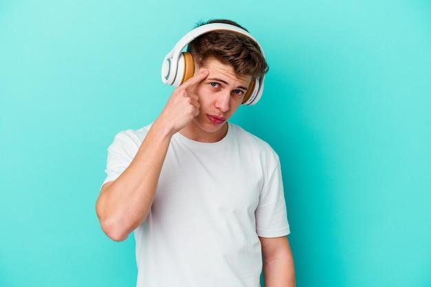 Młody człowiek, słuchanie muzyki w słuchawkach na białym tle na niebieskiej ścianie, wskazując świątynię palcem, myśląc, koncentruje się na zadaniu