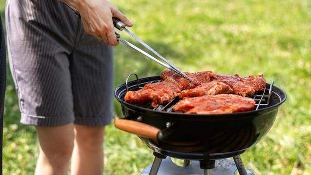 Młody człowiek smażenia mięsa na grillu. wokół zieleń. glamping