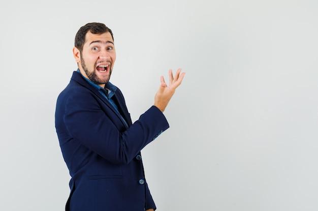Młody człowiek śmiejąc się, podnosząc rękę w koszuli, kurtce.
