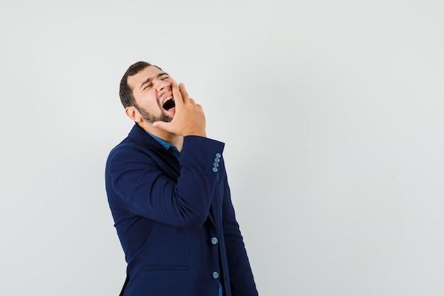 Młody człowiek śmiejąc się trzymając dłoń na ustach w koszuli, widok z przodu kurtki.