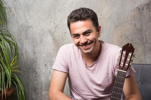 Młody człowiek śmiejąc się w pokoju trzymając gitarę.