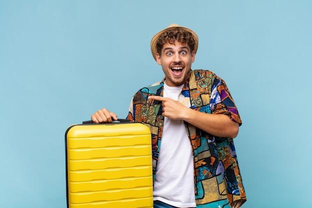 Młody człowiek śmiejący się, wyglądający na szczęśliwego, pozytywnego i zaskoczonego, realizujący świetny pomysł wskazujący na boczną przestrzeń kopii. koncepcja wakacji