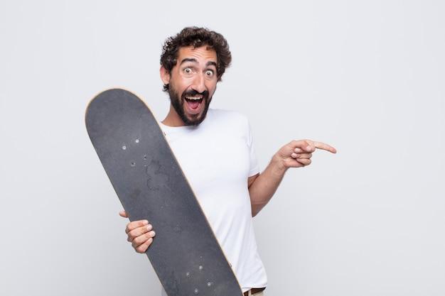 Młody człowiek śmiejący się, wyglądający na szczęśliwego, pozytywnego i zaskoczonego, zdając sobie sprawę ze świetnego pomysłu wskazującego na boczną przestrzeń kopii
