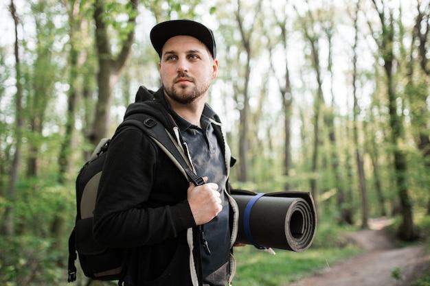 Młody człowiek spaceru w lesie z bagpack