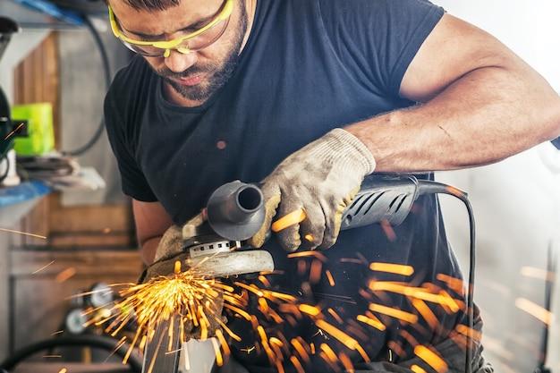 Młody człowiek spawacz szlifierka metalowa szlifierka kątowa w garażu