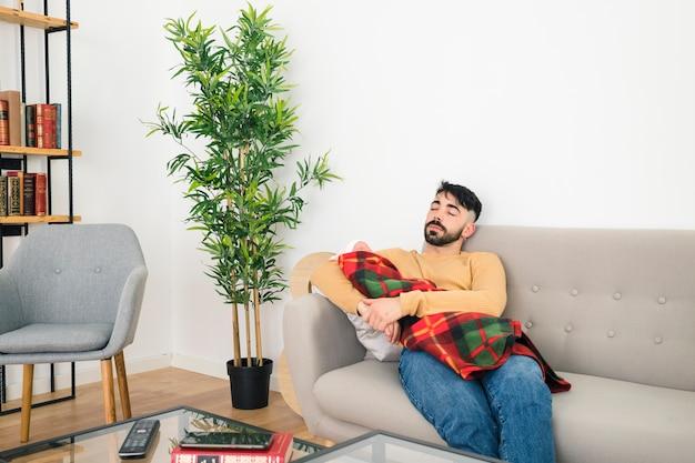 Młody człowiek śpi na kanapie, niosąc swoje dziecko w ręku