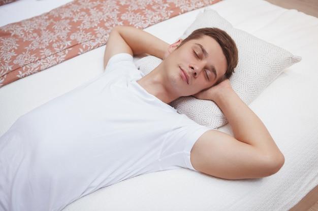Młody człowiek śpi na łóżku