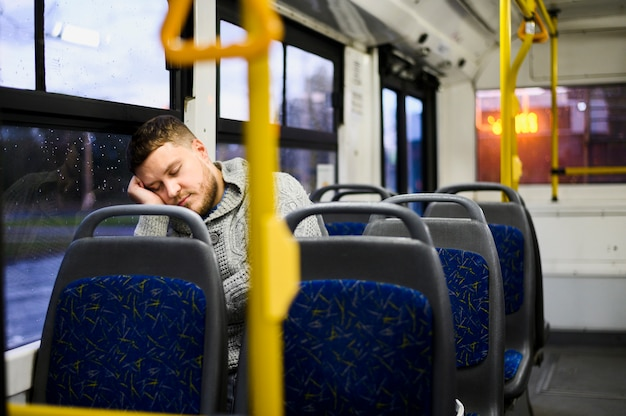 Młody człowiek śpi na siedzeniu autobusu