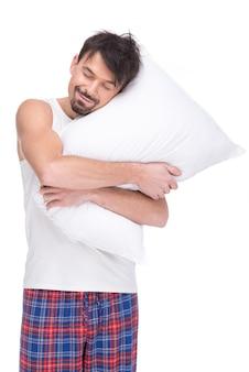 Młody człowiek śpi z głową na poduszce.