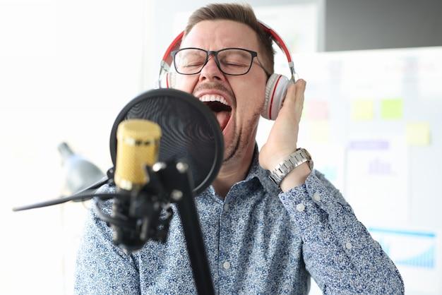 Młody człowiek śpiewa do mikrofonu w słuchawkach