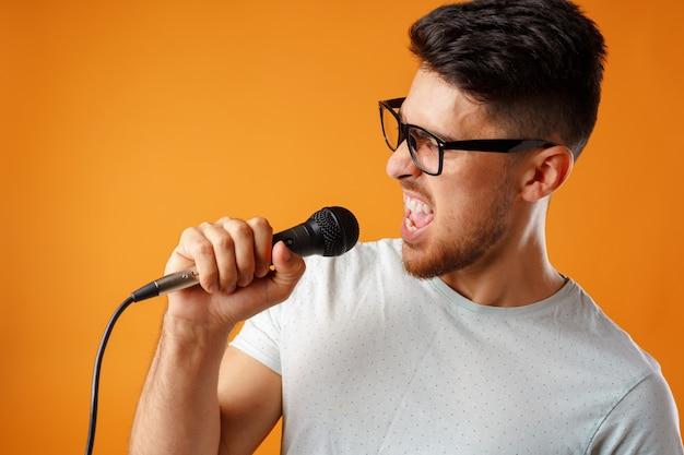 Młody człowiek śpiewa do mikrofonu