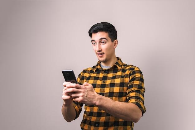 Młody człowiek spoglądający na telefon zadziwiony niewiarygodnymi wiadomościami lub postem w mediach społecznościowych